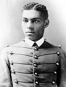 Cadet Henry O. Flipper in his West Point cadet uniform. It has three large round brass buttons left, middle and right showing five rows. The buttons are interconnected left to right and vice-versa by decorative thread. He is wearing a starched white collar and no tie. He is a lighter-colored African American with plated corn rows of neatly done hair. He is facing the camera and looking to the left of the viewer.
