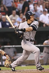 "A baseball player following through on a swing. The player is wearing a gray uniform and navy baseball helmet; the uniform has a navy blue ""NEW YORK"" on the front, and the helmet has a white interlocking ""N"" and ""Y"" logo."