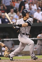 left-handed baseball player wearing a grey baseball uniform looks to the right as he follows through a swing with his bat.