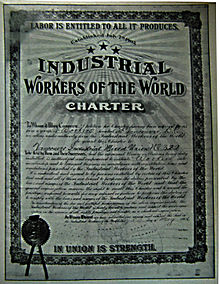 Framed, formal document featuring various IWW themes, cursive body text, hand-filled forms and a stamped seal.