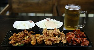 Korean fried chicken - ganjang chikin (coated with soy sauce), huraideu chikin (regular fried chicken), and yangnyeom chikin (coated with spicy sauce) with a glass of beer