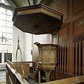 Interieur, overzicht van de preekstoel, staat voor de houten tussenwand die het schip van het koor scheidt, op de voorgrond een koperen doopboog - Beets - 20388569 - RCE.jpg