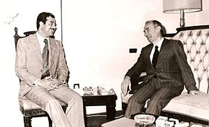 Saddam Hussein and Michel Aflaq seated, talking. Both wear suits.