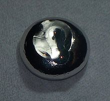 A flattened drop of dark gray substance