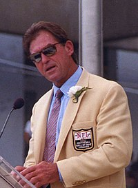 Jack Youngblood, 51-year-old white man dressed in gold jacket, blue shirt, tie and sunglasses, giving his Pro Football Hall of Fame induction speech in 2001.