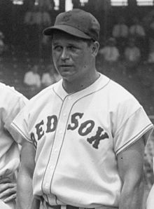 "A man in a white baseball jersey reading ""RED SOX"" across the chest and a dark baseball cap looks toward the left of the image"