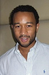 A picture of an African-American man with short back hair. He is wearing a white shirt with blue checkered lines in it.