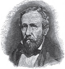 A man with receding black hair, a mustache, and a beard wearing a white shirt and black jacket