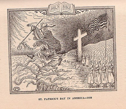 "In this 1926 cartoon, the Ku Klux Klan chases the Roman Catholic Church, personified by St. Patrick, from the shores of America. Among the ""snakes"" are various supposed negative attributes of the Church, including superstition, the union of church and state, control of public schools, and intolerance. KKK - St Patricks Dau.jpg"