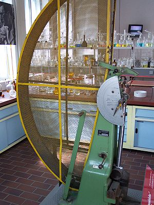 Charpy impact test - A vintage impact test machine. Yellow cage on the left is meant to prevent accidents during pendulum swing, pendulum is seen at rest at the bottom
