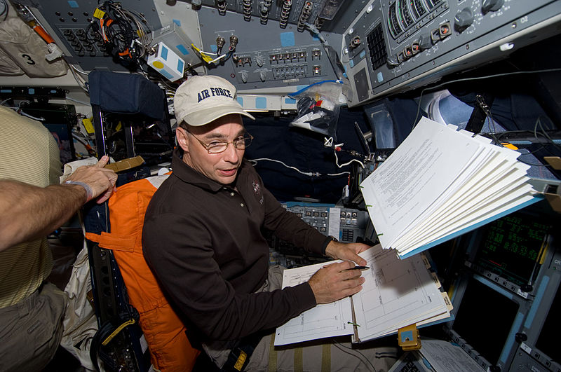 File:Lee Archambault going over a check list on the shuttle flight deck.jpg