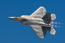 Dorsal view of F-22 in steep bank, ailerons clearly banking wings, modern camouflage, bright gold canopy, jet thrust possibly purple with afterburner and cloud-effect from leading edges of wings all suggesting high speed
