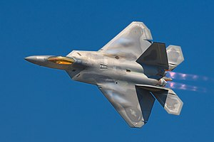 F-22 Raptor banking left in-flight, showing the top view of the aircraft. The engines with afterburners emit a pinkish glow. Aircraft ia mostly gray, apart from the gold cockpit window, with hints of bluish condensation on the wings.