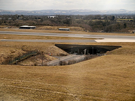 The A538 road runs beneath both runways via two separate tunnels. Part of the road is exposed between both runways. Manchester Airport A538 tunnel.jpg