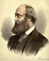 A dark-haired man with a huge beard, wearing a dark suit and a white shirt
