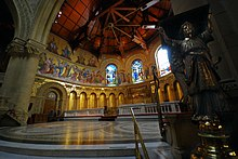 "A view into the chancel is framed on the right by the lectern supported by a standing brass angel. The chancel is semi-circular and has a roof on wooden beams. The upper walls have brightly coloured mosaics of prophets and angels. The white marble altar and mosaic reredos of ""The Last Supper"" can be seen."