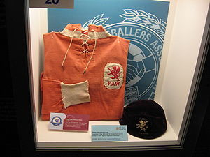 Billy Meredith - A Wales national team football shirt which was worn by Billy Meredith in the early 1900s, with Welsh cap. On display at the National Football Museum in Manchester.