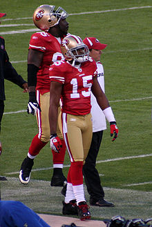 In the foreground, an American football player wearing a gold helmet, red jersey (number 15), gold pants and red socks walks along the sideline. Behind him, a man wearing a red cap and white t-shirt and another player in the same football uniform as the player in the foreground, walk in the same direction.