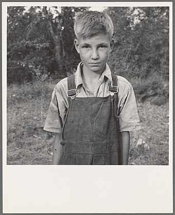 "Migratory boy in a squatter camp in Washington, 1939. Migratory boy in squatter camp. Has come to Yakima Valley for the third year to pick hops. Mother ""You'd be surprised what that boy can pick."" Washington, Yakima Valley.jpg"