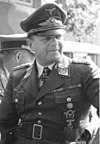 A man wearing a peaked cap and military uniform with various military decorations including an Iron Cross displayed at the front of his uniform collar.