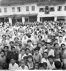Crowds throng a street in Kuching to witness the arrival of Australian Imperial Force (AIF) on 12 September 1945. Native population of Kuching.JPG