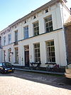 foto van Huis met gepleisterde empire gevel, eerste, helft 19e eeuw, deel uitmakend van het langgerekte complex 21-23