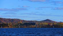A landscape photo of Onalaska Wisconsin taken in the fall from Lake Onalaka shows a sunny sky of blue above with clouds and the cool blue waters of Lake Onalaska below in the foreground.  Sandwiched between is a horizontal ribbon that shows the city elevated 100 feet above the water and tree covered bluffs in the not to distant background.  A few houses along highway 35 are barely visible.