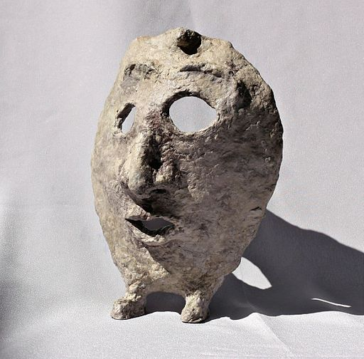 Paper mache mask with feet with grey background