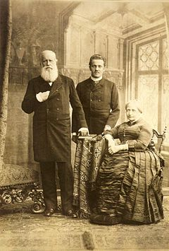 The white-bearded Emperor with his right hand tucked into his formal coat stands next to the right of the seated Empress who wears a hooped gown. In the background stands a younger man in formal dress.