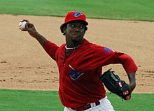 A dark-skinned man in a red baseball uniform and cap throwing a baseball with his right hand