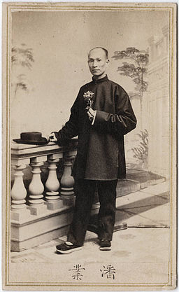 Photograph of a Chinese man holding a flower