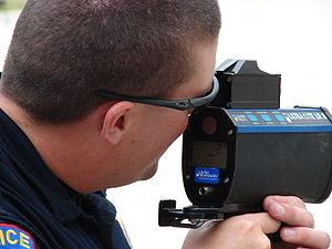 LIDAR traffic enforcement - Police officer operating a hand-held lidar speed detection device.