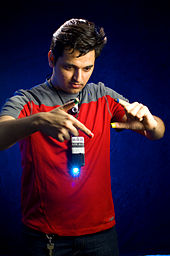 A man holds his hands in front of cellphone-sized pendant with a shining blue light. His fingertips are painted in different colors.