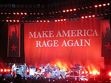 "The band onstage with a large banner reading ""Make America Rage Again"""