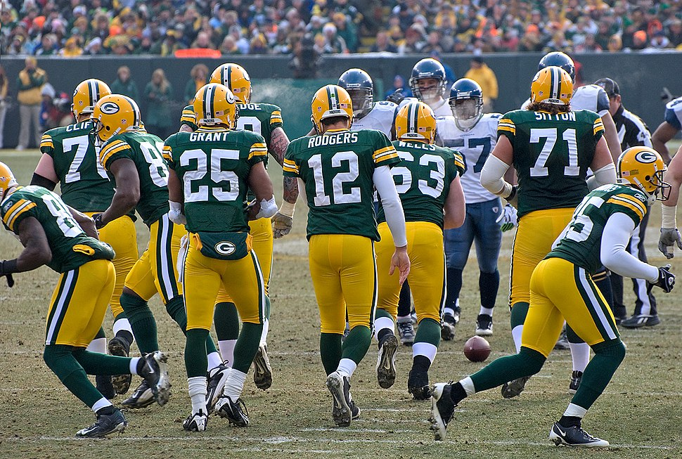Quarterback Aaron Rodgers (12) and the Packers break the huddle.