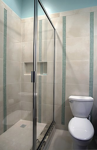 Bathroom - A residential bathroom in the US, with a shower, with rail-less screen and no bathtub, and a toilet.