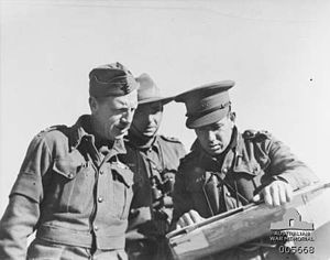 Three warmly dressed men in uniforms look at a map.
