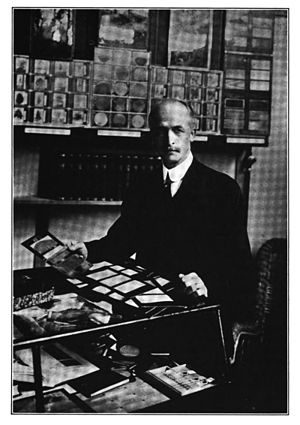 Romeyn Beck Hough - c. 1916 photograph of Romeyn Beck Hough displaying sections from American Woods. Behind are magic lantern slides.