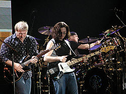 Color photo of 3 musicians on a stage, in the foreground, one man is holding a guitar, while the other is holding a bass guitar, and in the background a man playing drums.