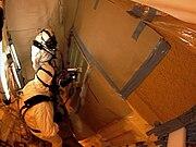 STS133 technicians spray foam on the tank