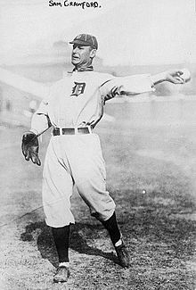 A baseball card of a player in a white and black uniform