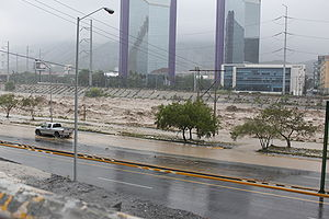 A flooded river in the city of Monterrey runs through the center of the image, and is partially flooding the roadways on both sides of its banks.