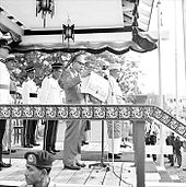 Ningkan holding papers containing the declaration, standing behind a microphone and in front of several guards on a podium