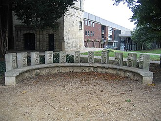 St Mary de Crypt Church, Gloucester - The semi-circular seat depicting the history of Gloucester behind St Mary de Crypt.