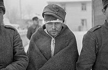 Soviet prisoners of war keep warm with their new clothes. The prisoner in the middle of the photo is staring at the ground with hollow eyes.