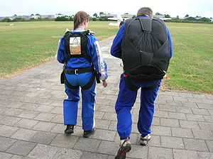 Tandem skydiving - Two people about to make a tandem jump. The instructor wears a parachute, while the student wears a harness to connect to the instructor.