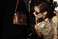 Tattooed lady looking at a handbag (15363214903).jpg