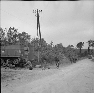 Green Howards - Men of the Green Howards mopping up German resistance near Tracy Bocage, Normandy, France, 4 August 1944. A knocked out half-track is visible on the left.