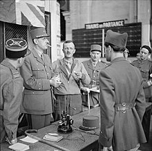 Six men in uniforms. De Gaulle is wearing his kepi and smoking a cigarette.