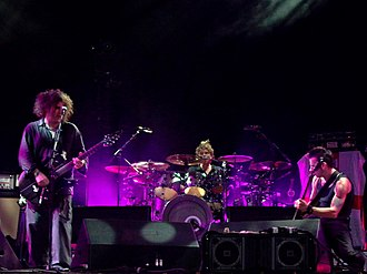 The Cure - The Cure in concert in 2004. From left to right: Robert Smith, Jason Cooper and Simon Gallup.
